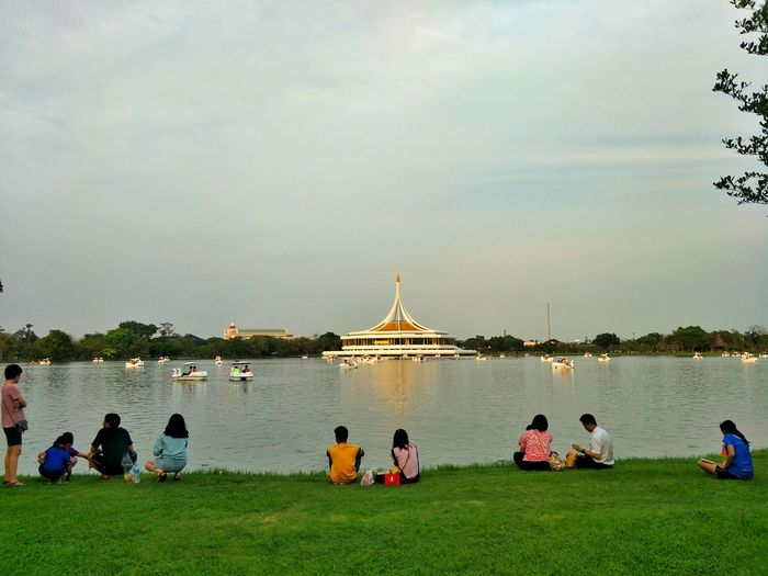 People sitting by lake against sky