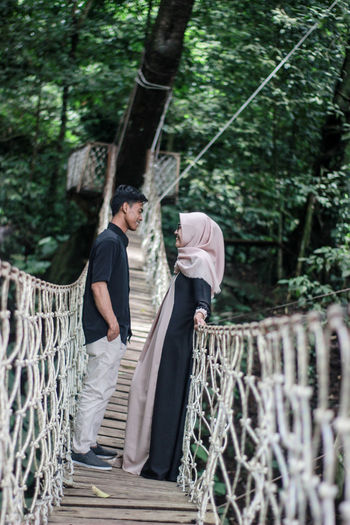 Young couple standing on footbridge at forest