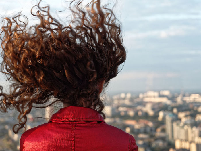 Rear View Of Woman With Tousled Hair Looking At Cityscape