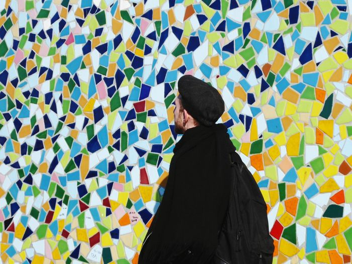 Young man standing against colorful mosaic wall
