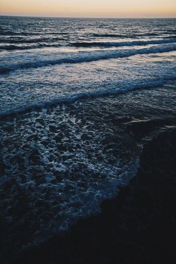 Close-up of sea against sky at sunset