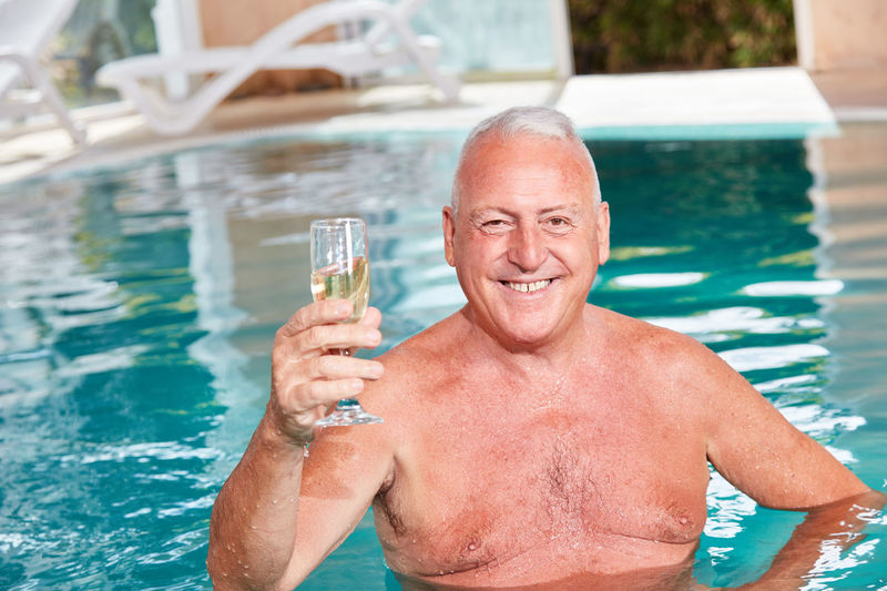 Portrait of a man drinking water in swimming pool