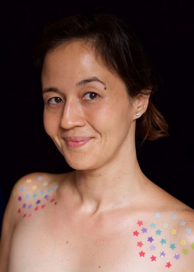 Portrait of shirtless woman against black background