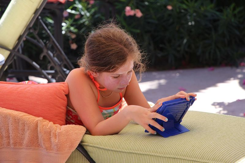 Girl using digital tablet while lying on seat