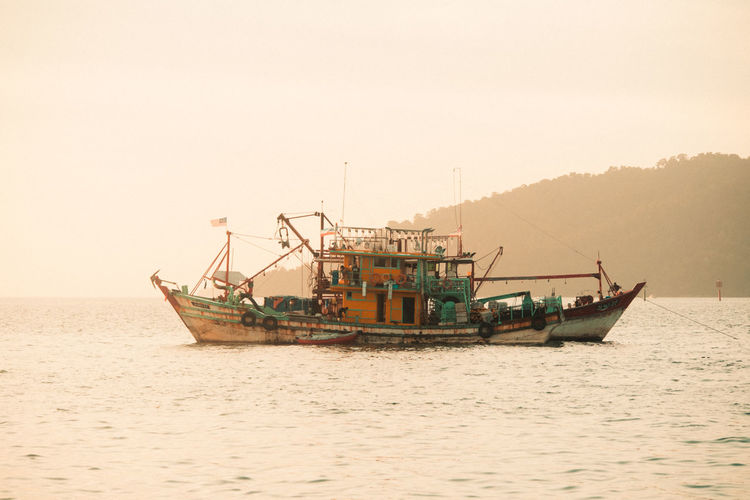 Fishing boat in sea against clear sky