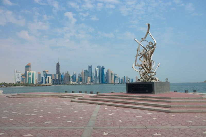 Doha City Skyline Doha Qatar Real Estate Sky Architecture Building Exterior Built Structure Water City Nature Sculpture No People Day Sea Statue Human Representation Building Cloud - Sky Representation Art And Craft Travel Destinations Office Building Exterior Cityscape