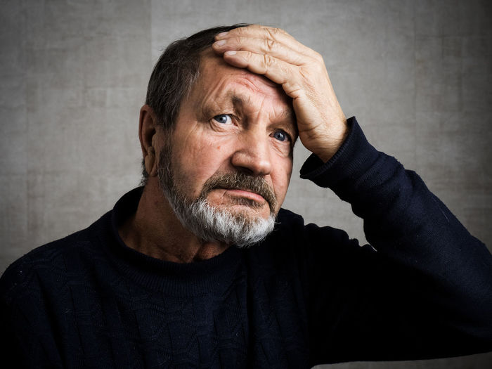 Thoughtful man with head in hands against wall