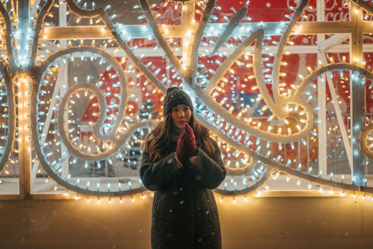 Christmas Christmas Decoration Portrait New Year One Person Standing Front View Young Adult Illuminated Young Women Real People Women Adult Leisure Activity Long Hair Lifestyles Three Quarter Length Architecture Looking Hairstyle Hair Smiling Beautiful Woman Warm Clothing