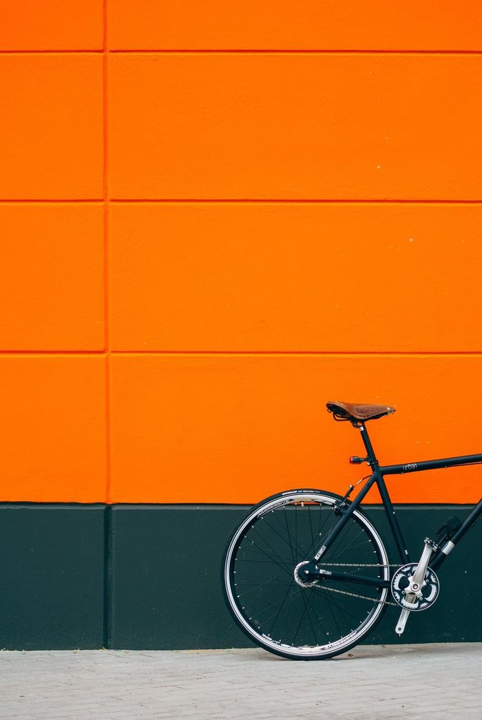 Cropped image of bicycle parked on footpath by orange wall