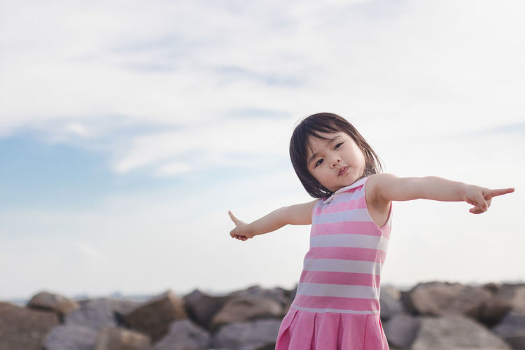 Arms Outstretched Arms Raised Casual Clothing Childhood Cloud - Sky Day Elementary Age Focus On Foreground Front View Girls Leisure Activity Lifestyles Looking At Camera Nature One Person Outdoors Portrait Real People Rock - Object Scenics Sky Standing Three Quarter Length Young Adult