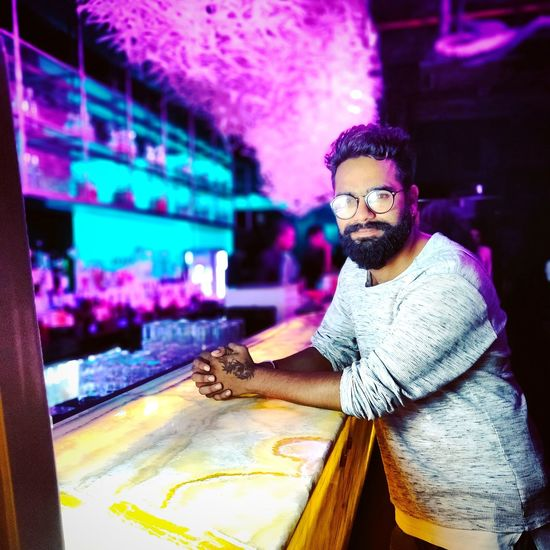Portrait of man standing at counter in illuminated club