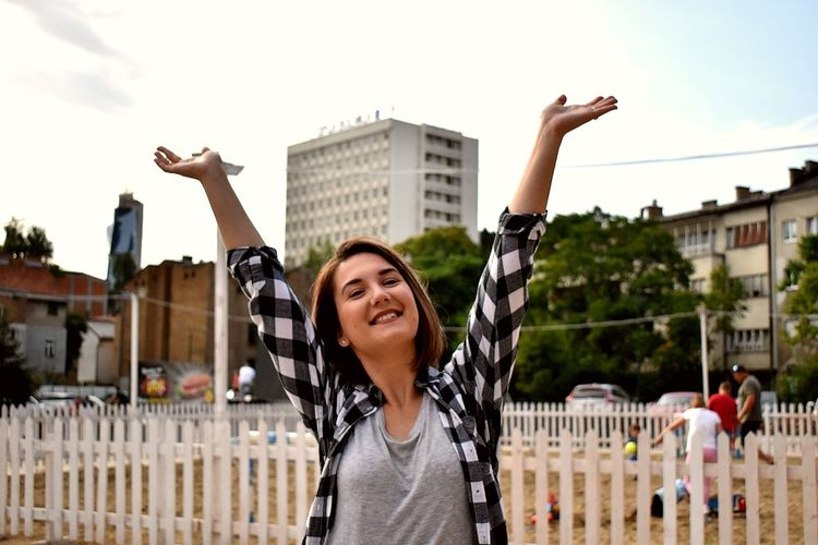 Portrait of smiling young woman with arms raised against buildings