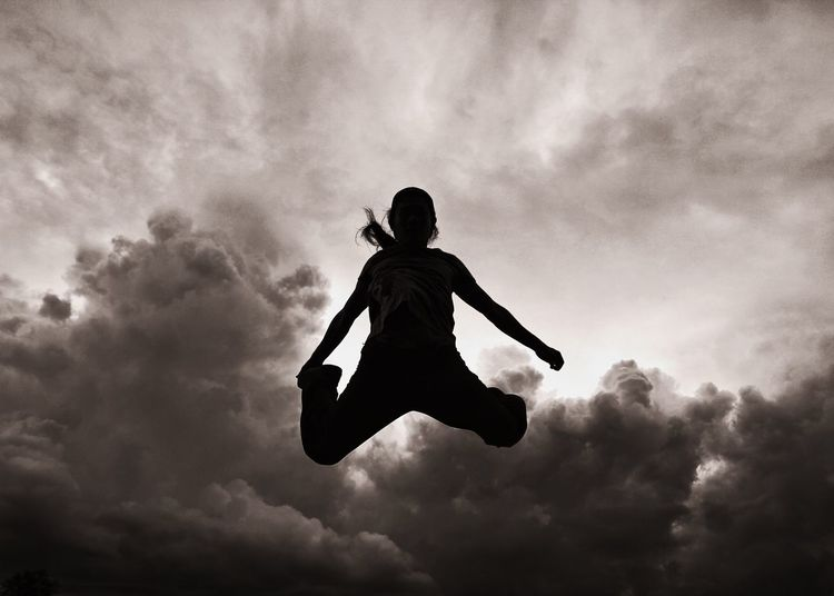 Silhouette Woman Jumping In Mid-Air Against Cloudy Sky