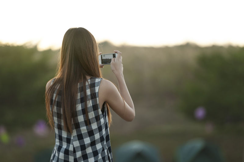 Rear view of woman photographing outdoors