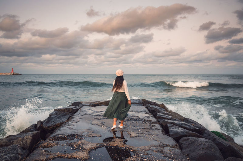 Woman on rock at beach against sky