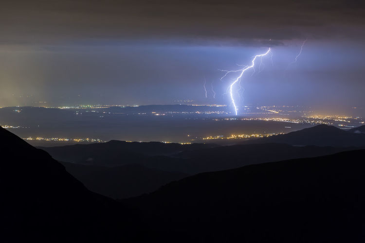Panoramic view of lightning over mountains against sky at night