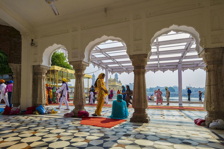 Amritsar, India, Women under the collonades in the Golden Temple Indoors  Sari Adult Architectural Column Colonnade Religion Sikh Arch Golden Tempel Amritsar Punjab Day Flooring Tourism Travel Destinations Women Arcade Building Group Of People Real People Architecture Editorial Use Only