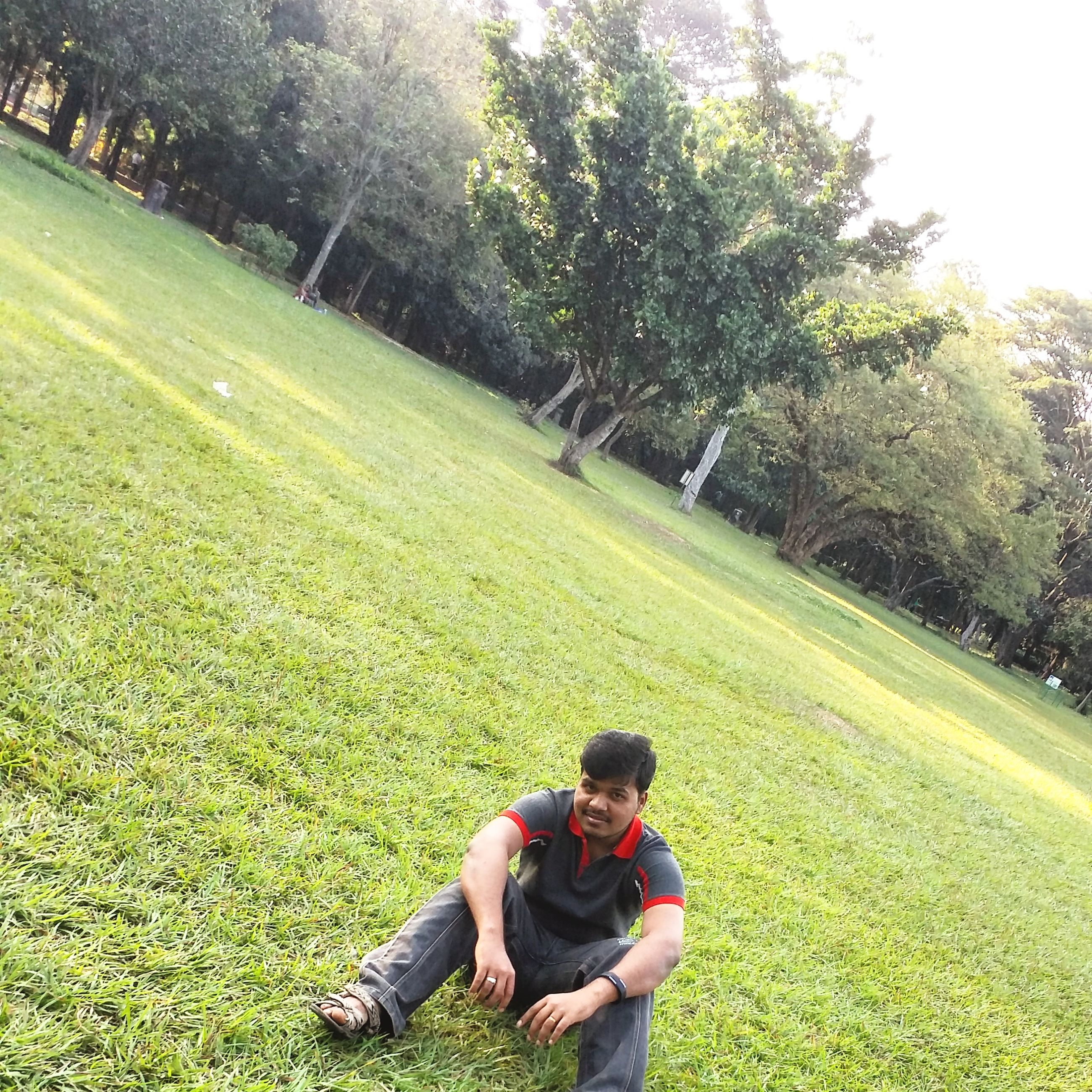 lifestyles, leisure activity, grass, casual clothing, green color, full length, field, relaxation, sitting, grassy, person, childhood, tree, men, landscape, nature, rear view