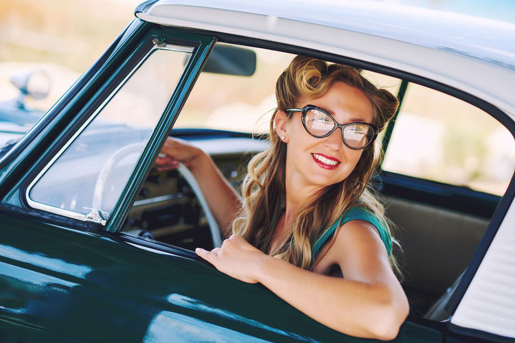 Beautiful happy woman sitting in a car. Retro styled Automobile Blonde Driver Summertime Transportation Woman Attractive Auto Beautiful Woman Caucasian Cheerful Eyeglasses  Eyeglasses  Eyewear Happiness One Person Outdoors Real People Retro Car Retro Styled Smiling Summer Vintage Cars Young Adult Young Women