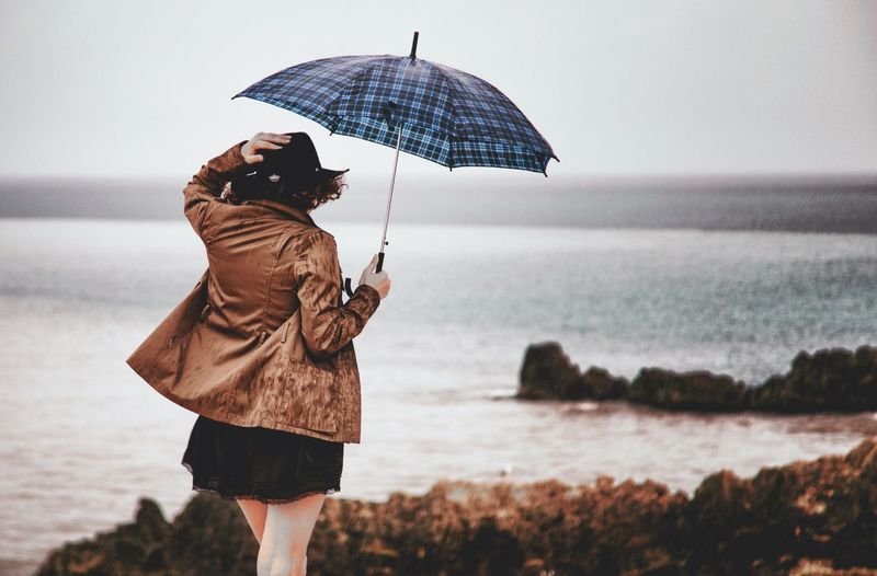 People And Places Rainy Day Rain Standing Lifestyles Leisure Activity Water Umbrella Holding Three Quarter Length Sea Rear View Casual Clothing Beach Vacations Rain Focus On Foreground Horizon Over Water Jacket Travel Person Tourist Clear Sky
