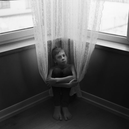 Portrait of girl against window at home