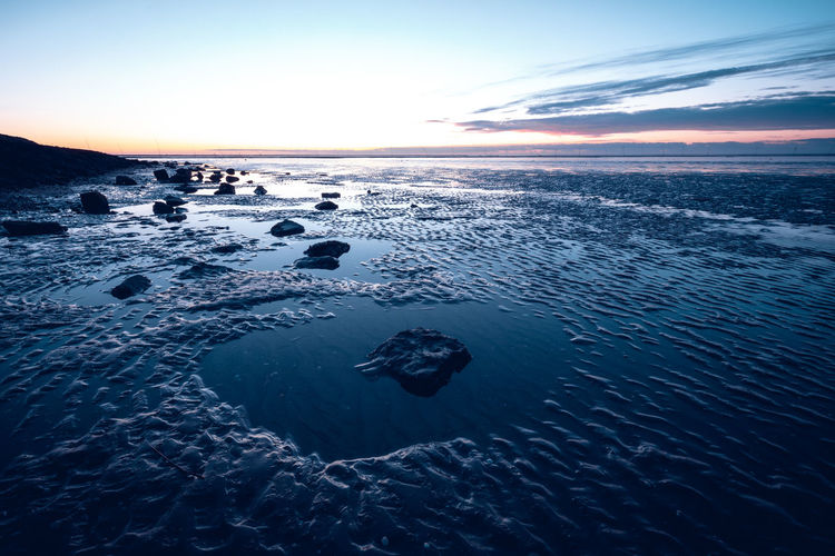 Mud flad at low tide with rock objects in the mud. Mud Flat Evening Sky Wattenmeer Water Sea Sky Horizon Over Water Beauty In Nature Scenics - Nature Nature Horizon Cloud - Sky Tranquility Tranquil Scene Underwater No People Beach Outdoors Land Rock Sunset Blue Rock - Object Solid Low Tide