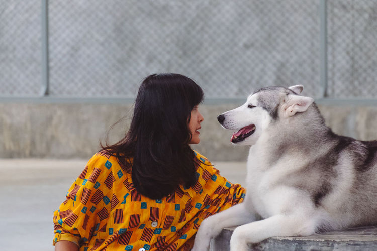 Mid adult woman with siberian husky sitting outdoors