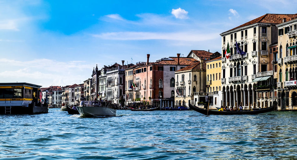 Boats sailing on grand canal by buildings in city