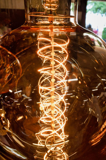 Decorative coil of a lightbulb Coil Lightbulb Illuminated Lighting Equipment Close-up Transparent No People Indoors  Glowing Glass - Material Electricity  Focus On Foreground Motion Light Filament Glass Light Bulb Electric Light Long Exposure Drinking Glass Blurred Motion Light - Natural Phenomenon Power Supply Tea Light