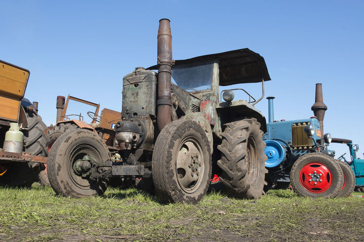 Old vintage tractors from a low angle on a blue sky Agriculture Tractor Oldtimers Land Vehicle Transportation Agricultural Equipment Clear Sky Agricultural Machinery Wheel Outdoors Blue Machinery Field