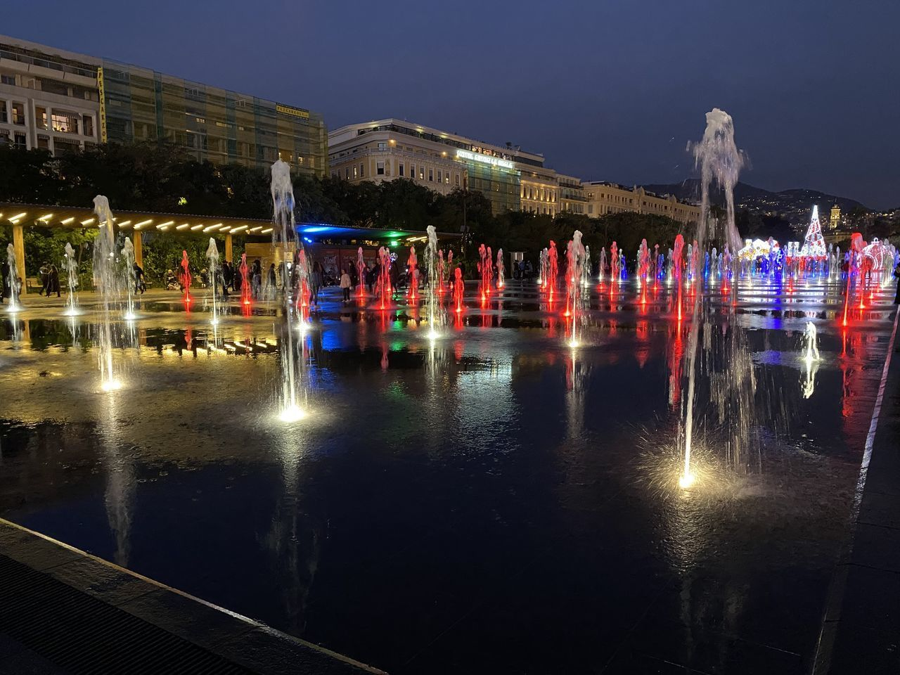 illuminated, reflection, water, night, architecture, built structure, building exterior, city, nature, group of people, sky, transportation, motion, waterfront, building, lake, large group of people, outdoors, travel destinations, light