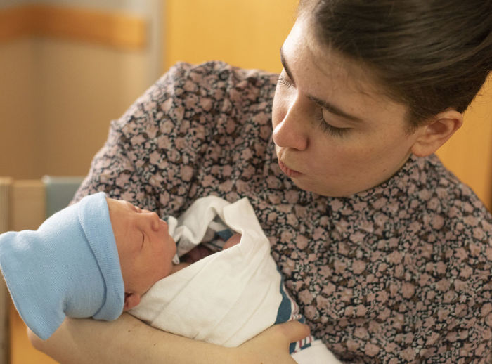A newborn infant boy is held by his older sister hours of the baby's birth. Indoors  Childhood Child Togetherness Love Newborn Positive Emotion Care Family Baby Young Females Women Adult Beginnings Family With One Child Portrait Son Innocence Healthcare And Medicine Sibling Siblings Hospital Brother Sister