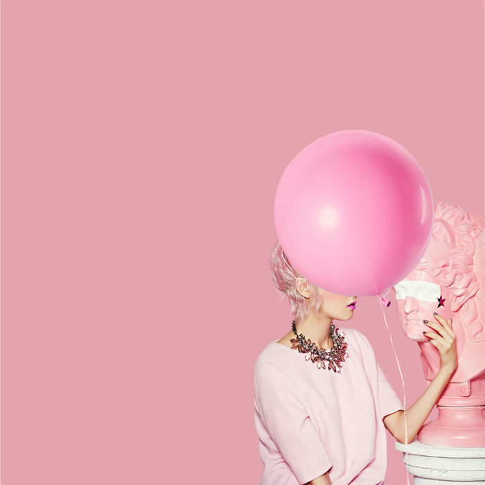 WOMAN STANDING ON PINK BALLOONS AGAINST COLORED BACKGROUND