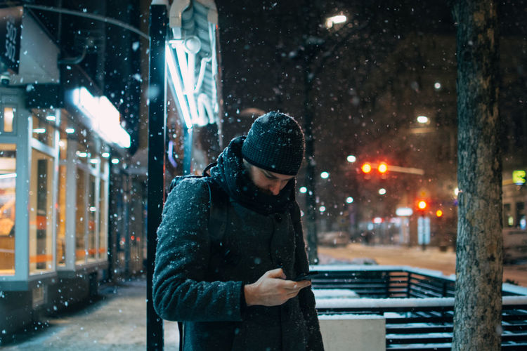 Man using smart phone on city street during winter