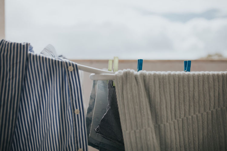 Close-Up Of Clothing Drying On Clothesline In Balcony