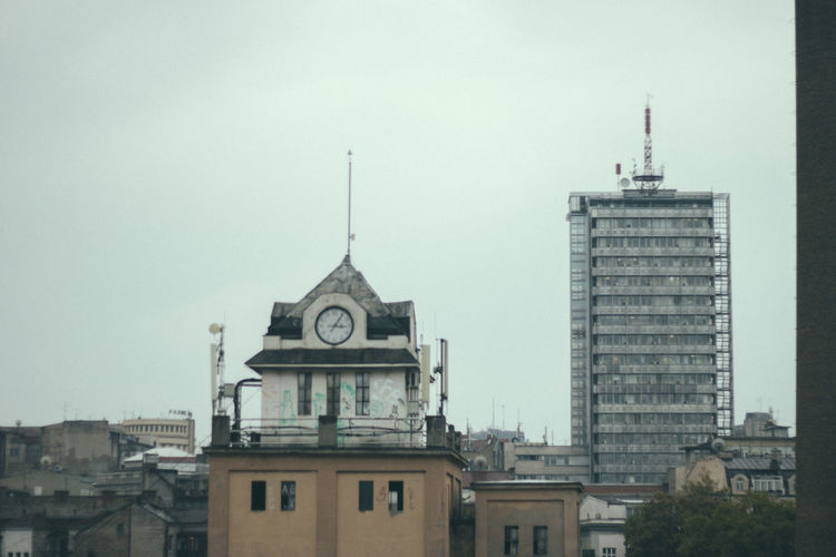 Clock tower in city against sky