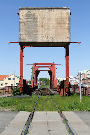 Railroad track in city against clear sky