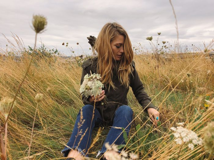 Young blond woman on a cloudy day holding flowers in a field of grass Wild Youth Free Blond Hair Happy Natural Beauty Natural Hippie Flowers EyeEm Selects Sky Lifestyles One Person Front View Plant Casual Clothing Real People Nature Leisure Activity Young Women Field Young Adult Land Sitting Day Women Long Hair Hair