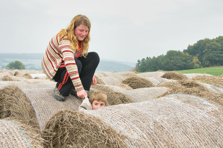 Woman with arms raised on farm against sky