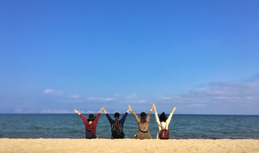 Rear view of friends with arms raised at beach against sky