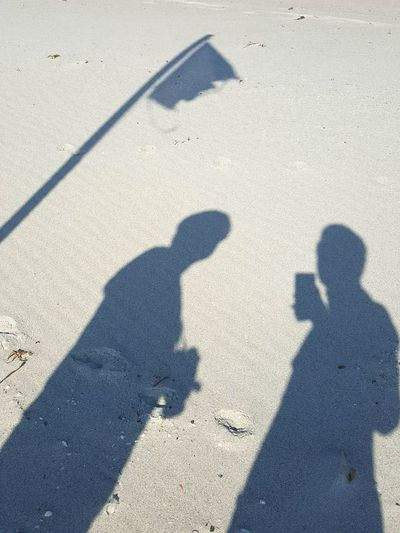 High angle view of people shadow on wet sand