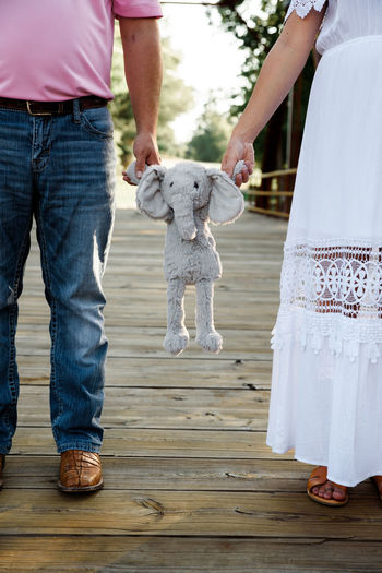 Low section of couple holding stuffed toy while standing outdoors