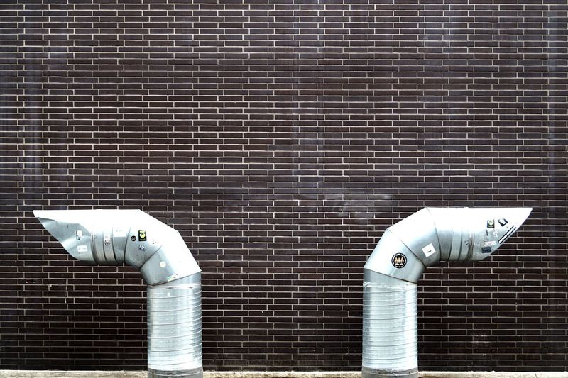 Close-Up Of Exhaust Pipes Against Brick Wall
