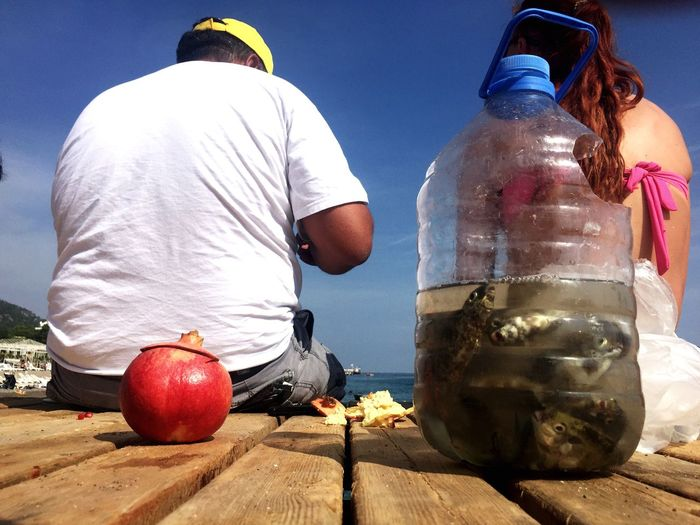 Rear View Of Man And Woman Sitting On Pier With Fishes In Plastic Jar