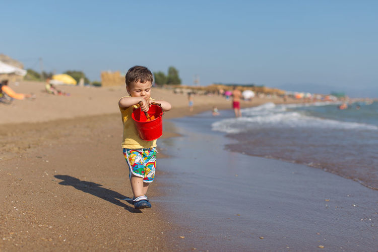 Full length of boy holding bucket on shore at beach