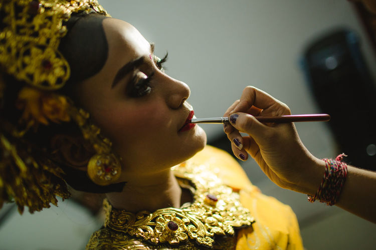 Cropped image of person applying lipstick to woman