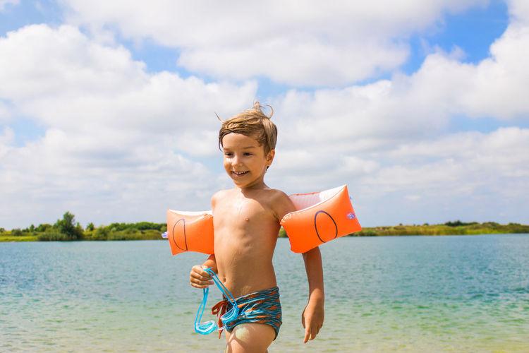 Boy Wearing Water Wings By Sea Against Sky