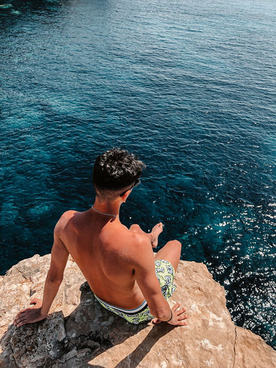 Rear view of shirtless man sitting on rock by sea