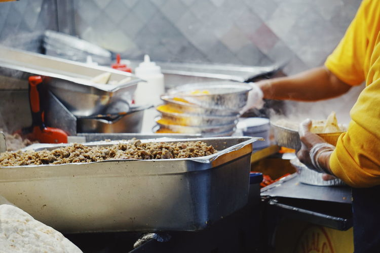 Midsection of people working at commercial kitchen