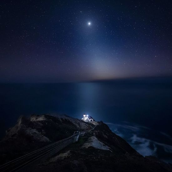 Aerial view of cliff by sea against sky at night